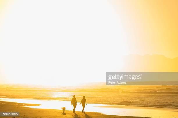 Couple and dog, sunrise, Muizenberg Beach