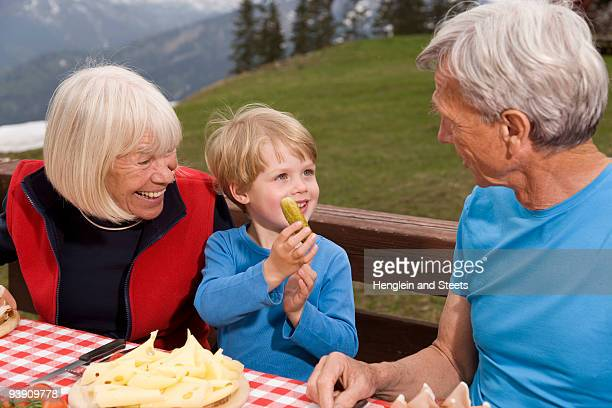 couple and grandson eating in mountains
