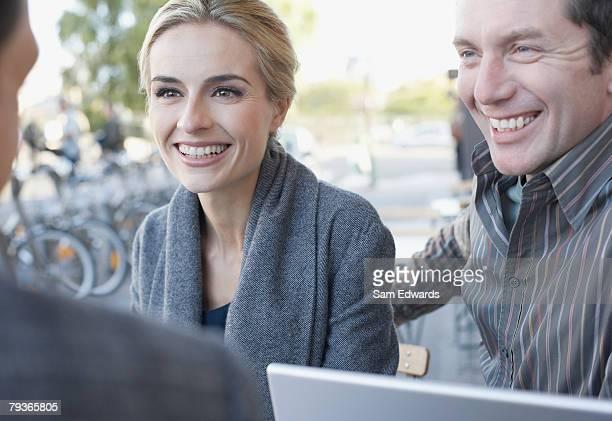 Coppia e uomo con portatile sul patio all'aperto