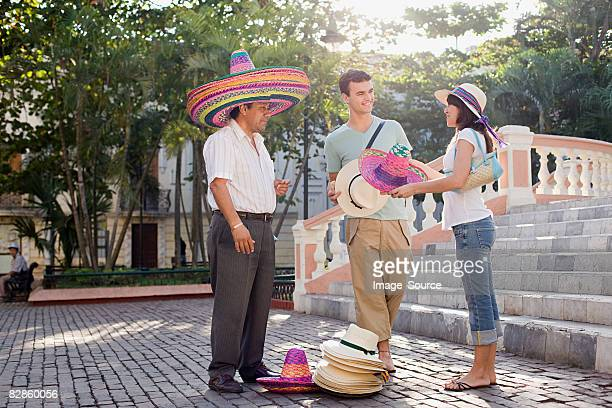 Couple and man selling hats