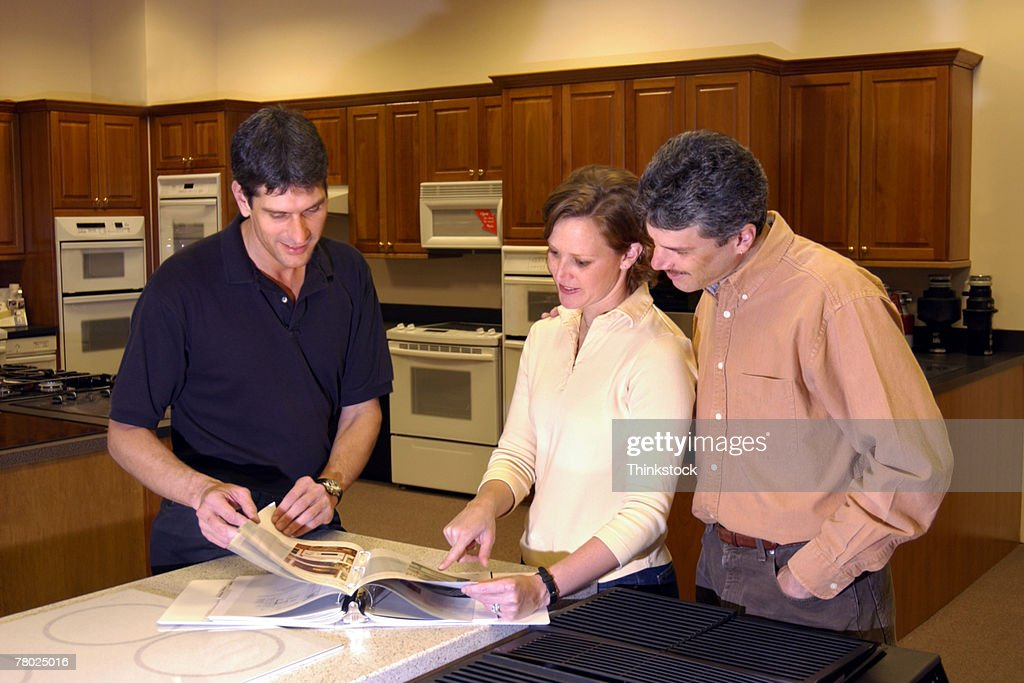 Couple and salesman looking at catalog of appliances