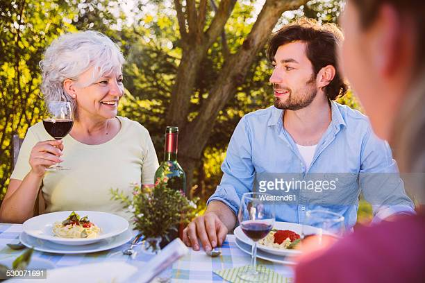 Couple and senior woman having dinner in garden