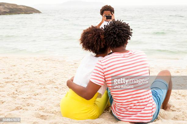 Couple and son taking photograph on beach