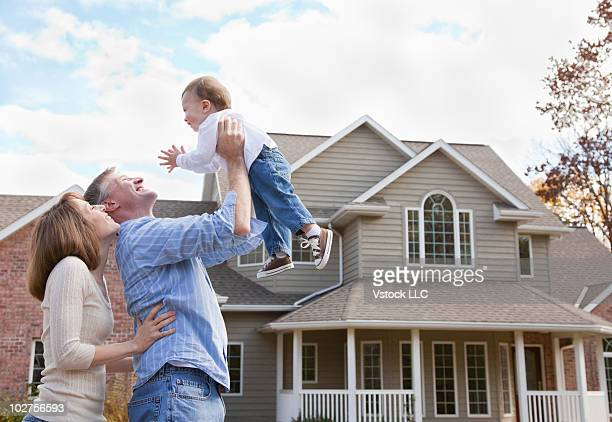Couple and their baby in front of their home