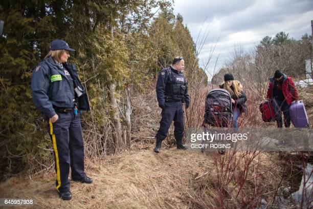 A couple and their baby who claimed they were from Syria cross the CanadaUS border near Hemmingford Quebec February 27 2017 under the watch of the...