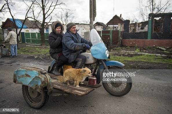A couple and their dog ride a motorbike with a sidecar in the village of Nikishino on April 21 2015 in the selfproclaimed Donetsk People's Republic...