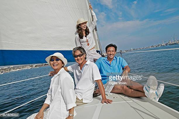 Couple and Their Mature Son and Daughter Sit at the Prow of a Sailing Boat, Smiling