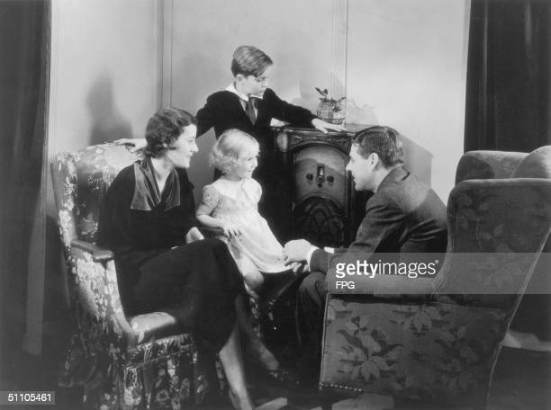 A couple and their two children gather around the radio in the living room circa 1935