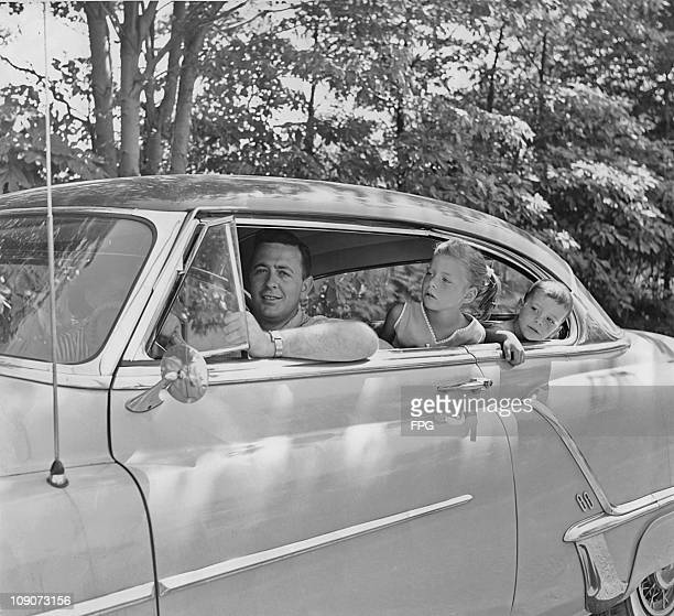 A couple and their two children in an Oldsmobile 88 coupe USA circa 1955