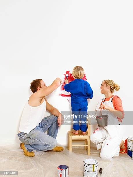 Couple and toddler boy painting wall