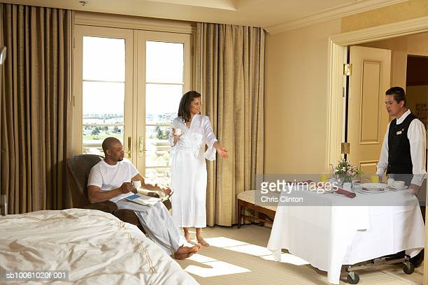 Couple and waiter delivering food in hotel room