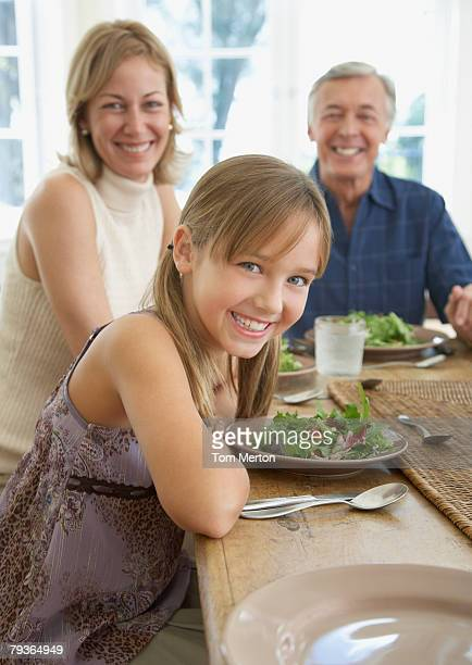 Couple and young girl at dining room table