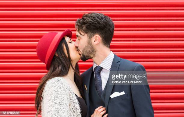 Couple are kissing in front of red shop shutter.