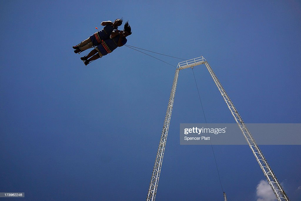 A couple are launched high above the Coney Island boardwalk while on a ride as people enjoy an afternoon on one of the hottest weeks in recent New York City history on July 18, 2013 in New York City. With daily temperatures in the high 90's and with the heat index making it feel in the triple digits, many New Yorkers are doing what they can to stay cool. A break from the heatwave is not expected until Saturday evening at the earliest.