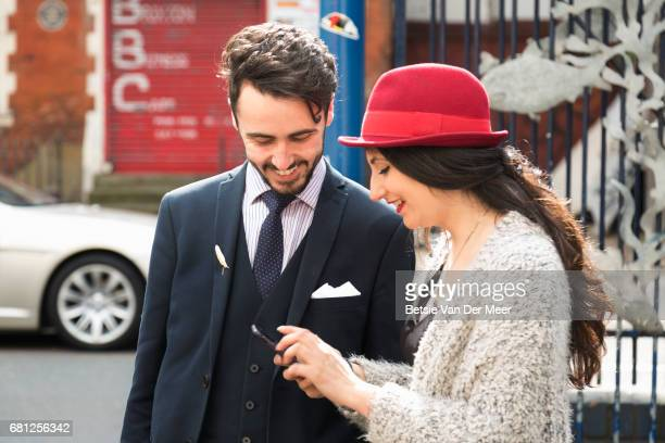 Couple are looking at mobile phone, standing in urban street.