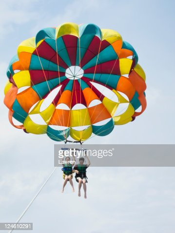 Couple are parasailing in sky.