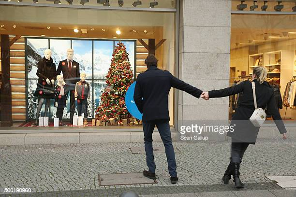 A couple are tempted by a shop display window on a shopping Sunday on December 6 2015 in Berlin Germany Stores are usually closed on Sundays in...