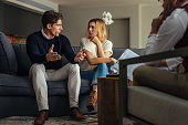 Couple arguing during therapy session with psychologist. Man and woman sitting on couch and talking while psychologist listening them.