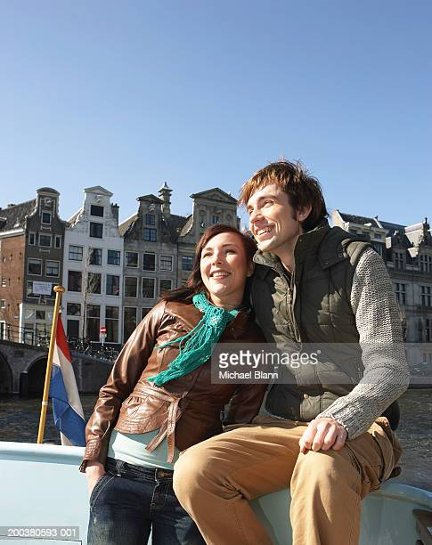 Couple arm in arm on boat on canal, smiling, low angle view