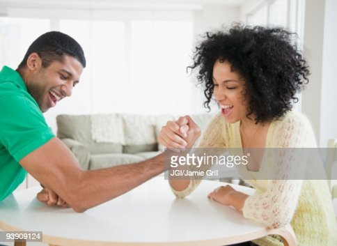 Couple arm wrestling at table