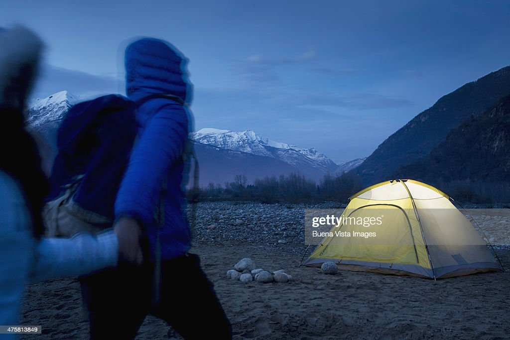 Couple arriving at their tent at night : Stock Photo