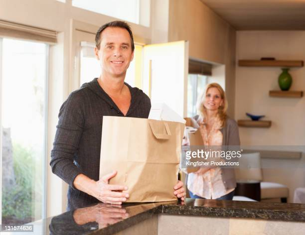 Couple arriving home with groceries