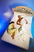 Couple asleep in bed, man hogging sheets