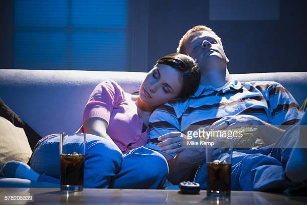Couple asleep on sofa with bowl of popcorn
