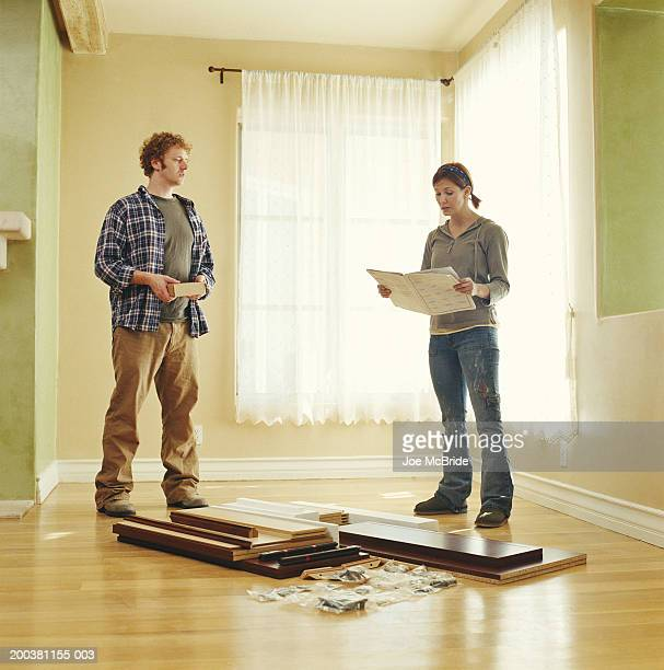 Couple assembling furniture, woman holding instructions