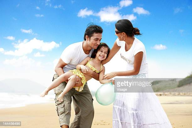 Couple at a beachside with their daughter