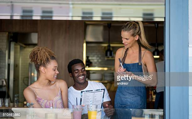Couple at a cafe ordering to the waitress