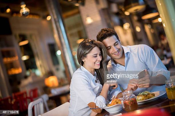 Couple at a restaurant looking at a cell phone