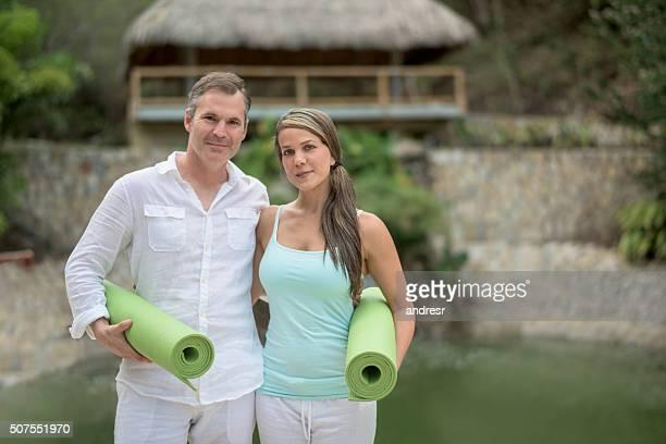 Couple at a spa holding yoga mats