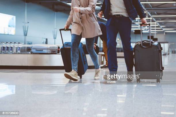 Couple at airport terminal with suitcase