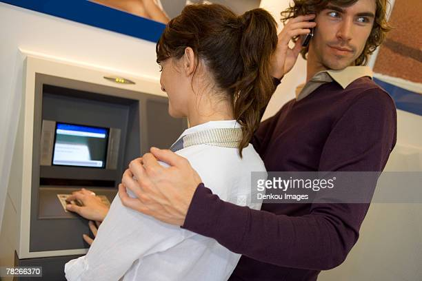 A couple at an ATM machine.