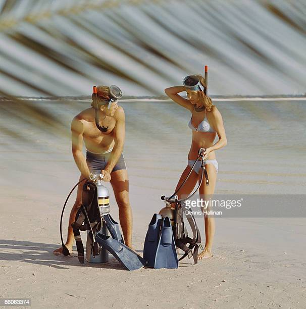 Couple at beach preparing scuba diving equipment