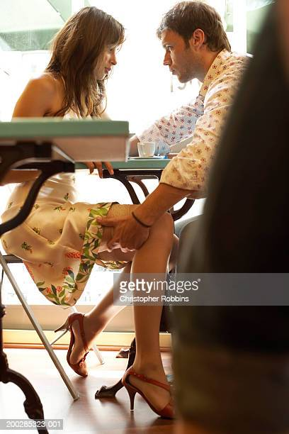 Couple at cafe table, man holding woman's leg