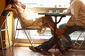 Couple at cafe table, man rubbing woman's ankle beneath table