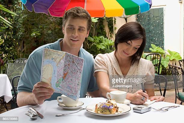 Couple at cafe with food and map
