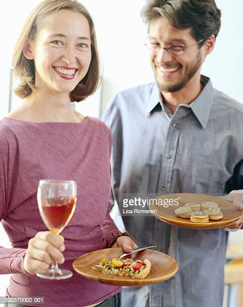 Couple at cocktail party, woman holding plate and wine glass