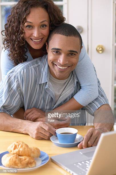 Couple at Dining Table with Laptop and Breakfast