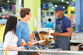 couple paying at hardware store till point