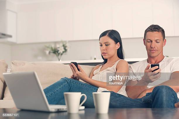 Couple at home both using mobile phones.