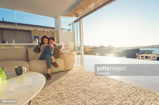 Couple à la maison à l'aide d'une tablette numérique.