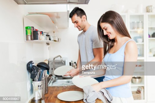 Couple at home washing dishes.