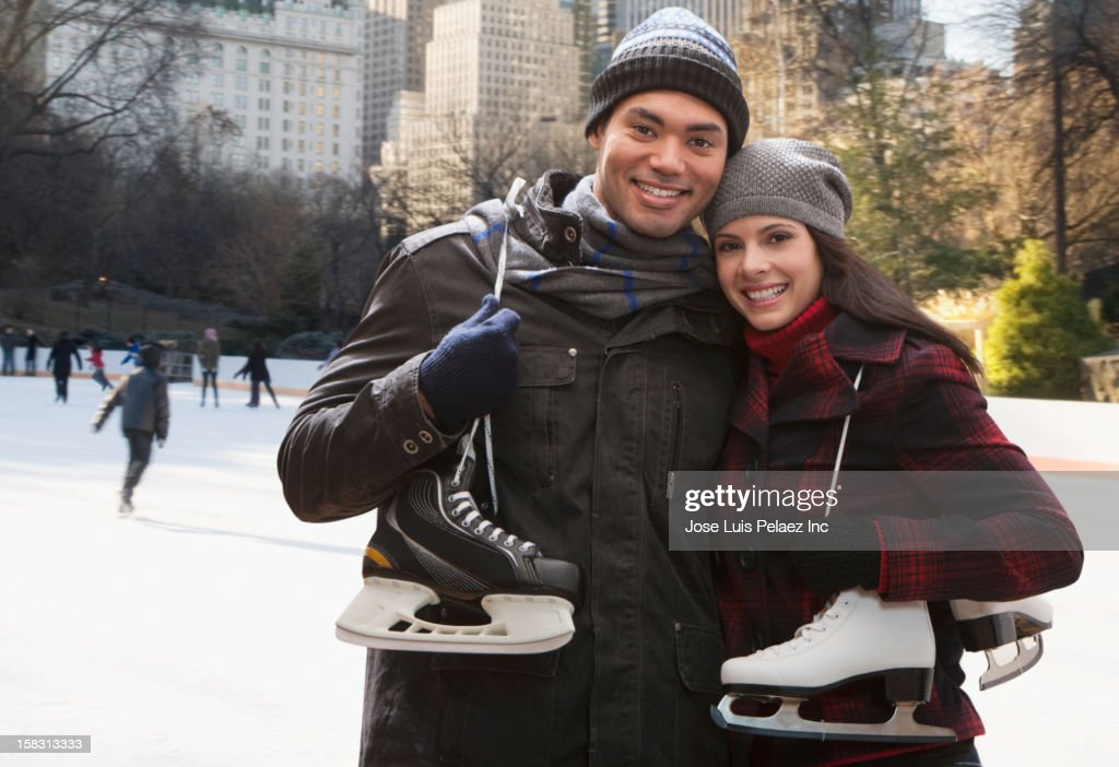 Couple at ice rink holding skates