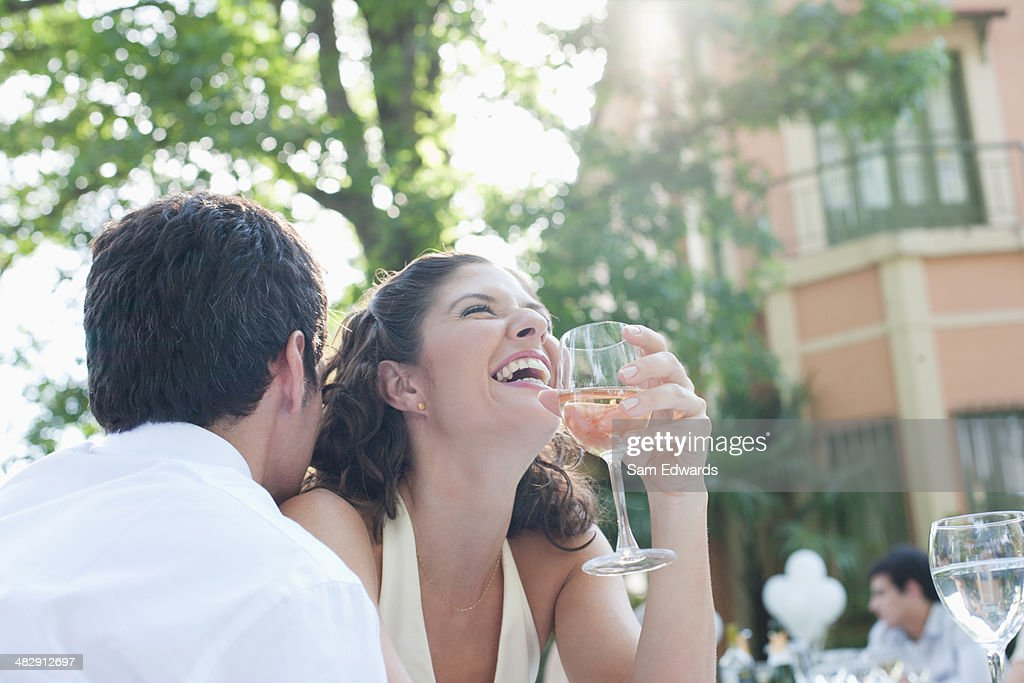 Couple at outdoor party with white wine laughing : Stock Photo