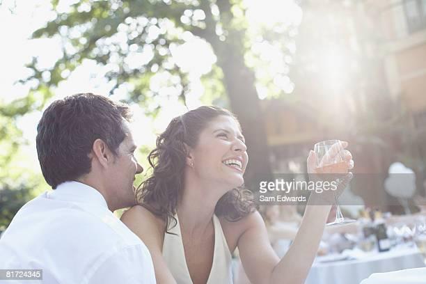 Casal ao ar livre com vinho branco rir Festa