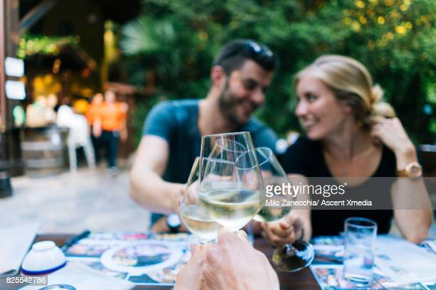 Couple at outdoor restaurant celebrating with wine