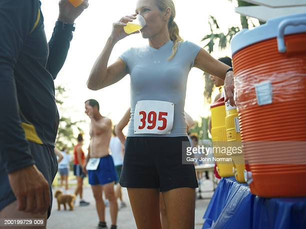 Couple at race drinking near beverage table, close-up